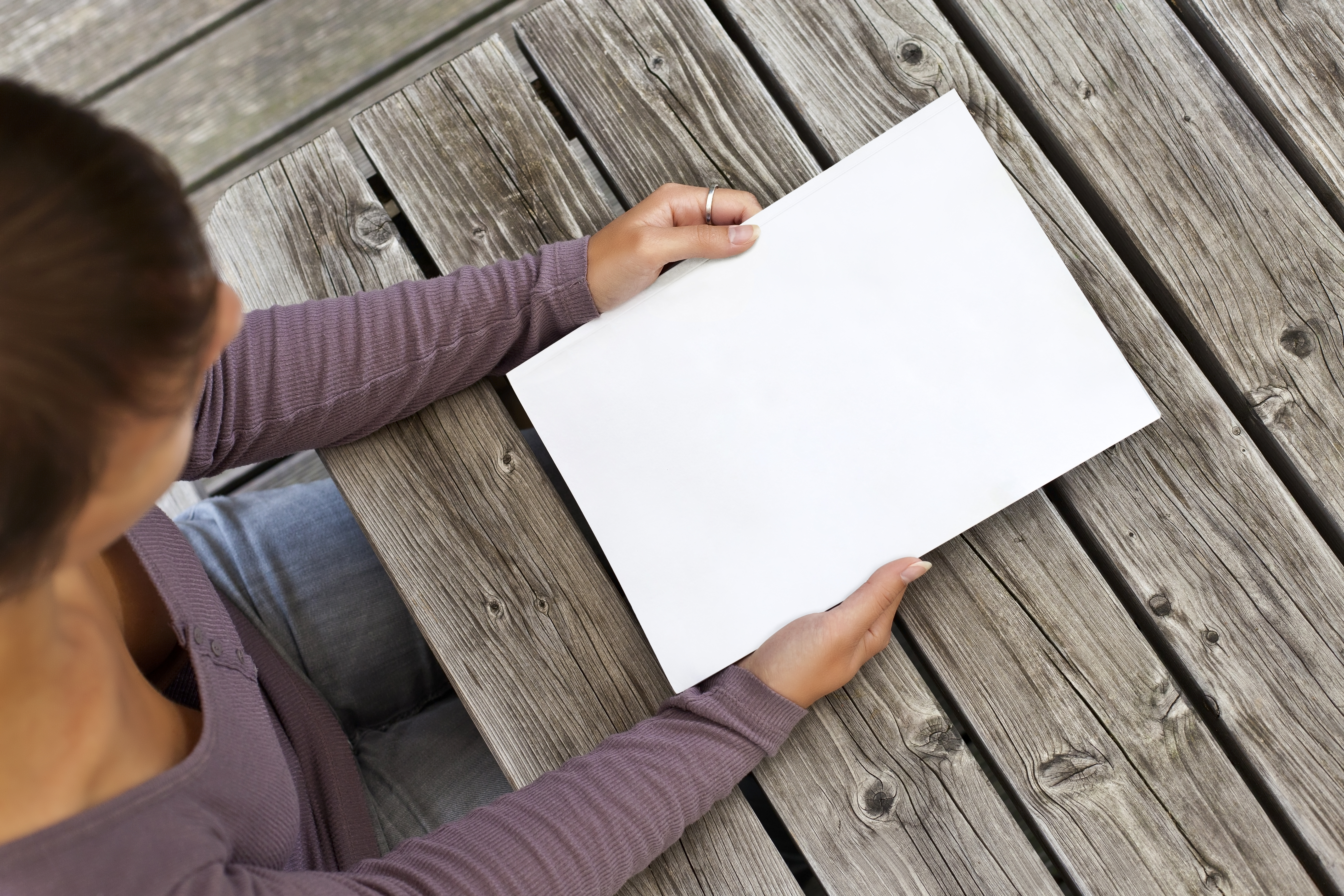 Woman in a purple shirt holding a white pad of paper, looking down.