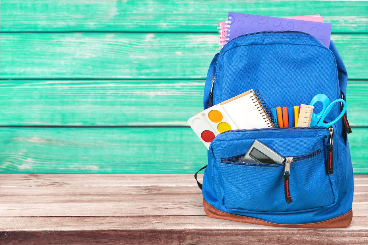 Photo shows a dark blue backpack. Backpack contains school supplies such as scissors, a note-pad, and painting tools. Backpack is against a light blue background and is placed on a wooden table.